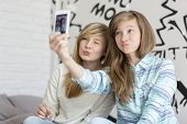pic of pouting  - Cute sisters pouting while taking photos with smart phone at home - JPG