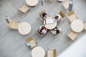 picture of canteen  - High angle view of businesswomen doing paperwork in office canteen - JPG