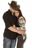 stock photo of snuggle  - A cowboy holding on to his woman close snuggled in his arms - JPG
