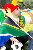 soccer fan blowing vuvuzela on field