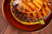 pic of burger  - Burger with grilled pineapple on dish without top bun shallow dof focus on pineapple - JPG