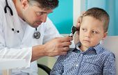 stock photo of otoscope  - Pediatrician using otoscope to examine boy