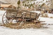 pic of wagon wheel  - Dilapidated wagon on a winter day in a Montana ghost town  - JPG