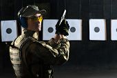 picture of shooting-range  - Man shooting with gun at a target in shooting range - JPG