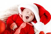 foto of christmas baby  - Cute newborn baby wearing Santa Claus hat sleeping in basket - JPG