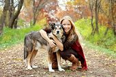 stock photo of shepherds  - A thirty year old woman is stopping to hug her German Shepherd dog as they are walking through the fallen leaves in the woods on an Autumn day - JPG