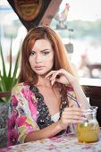 stock photo of woman red blouse  - Attractive red hair young woman with bright colored blouse drinking lemonade on a terrace - JPG