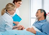 stock photo of congrats  - doctor talking to patient in hospital - JPG