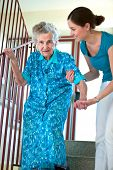 foto of neat  - Senior woman is climbing stairs with caregiver - JPG