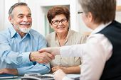 pic of lawyer  - senior couple smiling while shaking hand with financial advisor - JPG