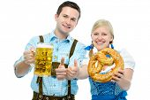 picture of stein  - Couple in traditional bavarian tracht holding Oktoberfest beer steins and pretzel - JPG