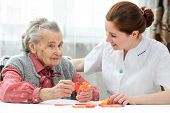 image of geriatric  - Nurse helps the senior woman jigsaw puzzle to solve in a nursing home - JPG