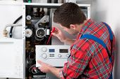 picture of gas-pipes  - Technician servicing the gas boiler for hot water and heating - JPG