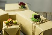 stock photo of embellish  - Gifts wrapped in kraft paper tied with twine and embellished with natural details - JPG
