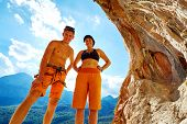 image of cave woman  - couple of climbers standing in a cave under arch on blue cloudy sky background and looking at the camera - JPG