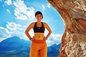 picture of cave woman  - girl climber standing in a cave under arch on blue cloudy sky background and looking at the side - JPG