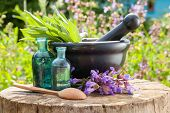 stock photo of perfume  - Black mortar with sage herbs glass bottles of essential oil outdoors. Herbal medicine.