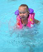 picture of kiddie  - Outdoor portrait of a cute little caucasian girl child with happy  facial expression having great fun while swimming in the pool - JPG