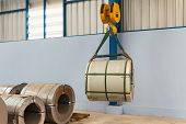 stock photo of coil  - Lifting steel coil by overhead crane - JPG