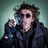 stock photo of anarchists  - Punk guy with glasses smoking cigaret - JPG