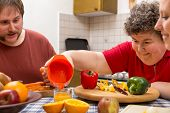 stock photo of disability  - a mentally disabled woman and two caretakers cooking together - JPG