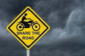 stock photo of warning-signs  - Share the Road Warning Sign An road warning sign with words Share the Road and a motorcycle icon with stormy sky background - JPG