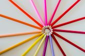 stock photo of color wheel  - Brightly coloured pencil crayons from the red side of the colour spectrum are arranged into a circle or wheel making a burst or spoke effect - JPG