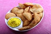 stock photo of holi  - gujia indian traditional snacks for holi festival with yellow color in bowl - JPG