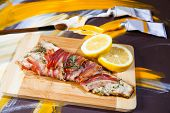 picture of bacon  - Trout fish rolled in bacon with lemon on painted background - JPG