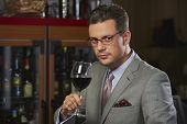 stock photo of posh  - Portrait of sophisticated confident wealthy gentleman in stylish suit toasting with glass of wine against blurred restaurant background - JPG