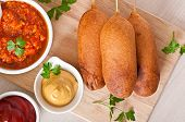 pic of wiener dog  - Homemade corn dogs with sauces on table - JPG