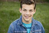 picture of denim wear  - Smiling teenage boy outside wearing denim jacket horizontal format 13 yrs old - JPG