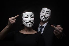 image of guy fawks  - two members of anonymous activist hacker group with mask studio shot - JPG