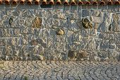 stock photo of old stone fence  - stone fence village house in Bulgaria in the evening light - JPG