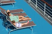 Mother With Daughter Lies On Deck-chair On Upper Deck Of Cruise Ship