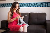 pic of quilt  - Beautiful young pregnant woman knitting a quilt for her baby at home - JPG