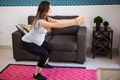 pic of pregnancy exercises  - Full length view of a young pregnant mother exercising and doing squats at home - JPG
