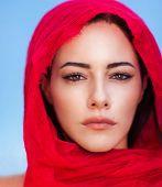 stock photo of arabian  - Closeup portrait of beautiful arabic woman wearing red headscarf over blue sky background - JPG