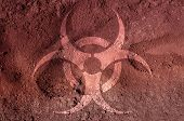 picture of biohazard symbol  - A biohazard symbol on soil with tracks - JPG