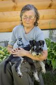 picture of schnauzer  - Senior woman hugs her black and silver miniature schnauzer dog in countryside  - JPG