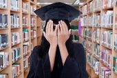 stock photo of peek  - Female student standing in the library while wearing graduation gown and peeking through her fingers - JPG