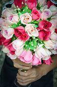 stock photo of bunch roses  - Two hand holding colorful bunch rose made from fabric - JPG