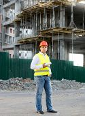 picture of scaffold  - Foreman in jacket and helmet posing against building in scaffolding - JPG
