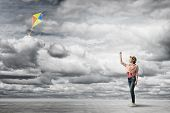 picture of kites  - Teenager girl in jeans playing with flying kite - JPG