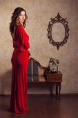 pic of red back  - Girl in a red dress standing in retro room back and turned her head - JPG