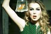 stock photo of goldfish  - Tempting young girl with bright makeup and blonde curly hair holding cellophane package aquarium with goldfish horizontal photo - JPG