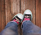image of pink shoes  - a wide angle photo of a pair of generic looking shoes like converse sneakers with pink shoe laces on a vintage wooden background making a emotion gesture by pointing one foot in - JPG