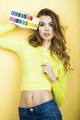 image of paint palette  - Pretty sensual young girl in blouse and blue jeans holding colorful paint palette standing on yellow wall background vertical picture - JPG