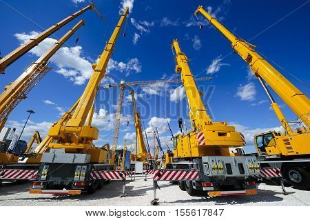 poster of Mobile construction cranes with yellow telescopic arms and big tower cranes in sunny day with white clouds and deep blue sky on background, heavy industry