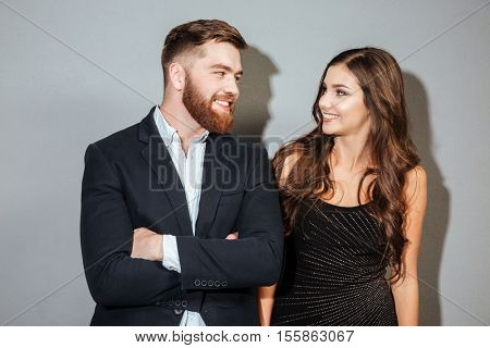 Happy smiling couple in formal wear looking at each other over gray background